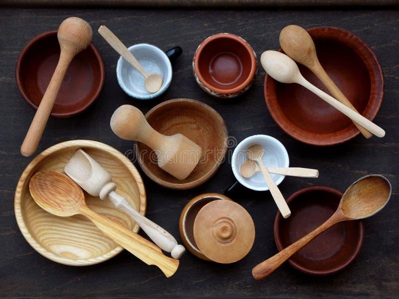 Ceramische, houten, klei lege met de hand gemaakte kom, kop en lepel op donkere achtergrond Het werktuig van het aardewerkaardewe stock foto