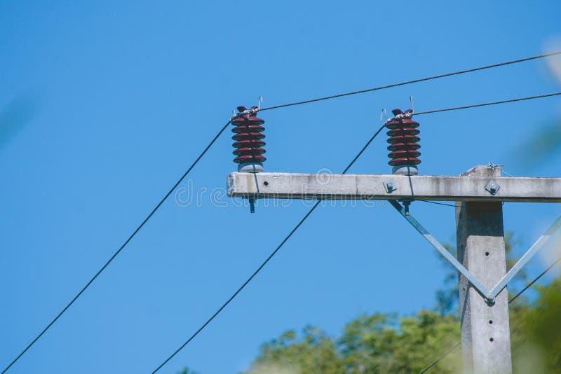 Ceramische isolatie voor het elektrische kabel hangen op de elektrische pyloon met blauwe hemelachtergrond stock foto's