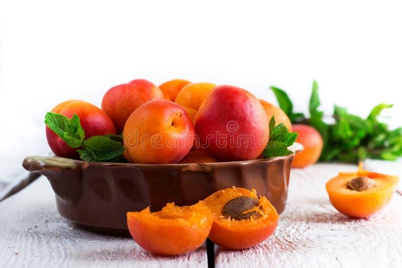 Ceramische kom met organische rijpe abrikozen royalty-vrije stock afbeelding