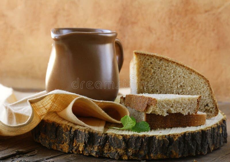 Ceramische kruik met melk en een zwart brood van de broodrogge stock foto's