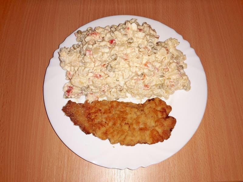 Ceramische plaat met aardappelsalade en kotelet, allen op een tafelkleed met een overheersend purper motief royalty-vrije stock foto