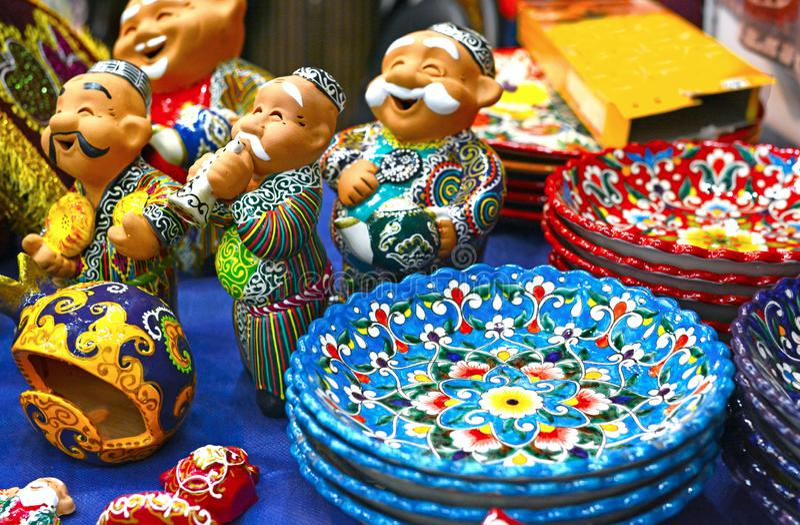 Ceramische platen en cijfers van Oezbekistaanse mensen n in traditionele kleding - robe en een skullcap, geschilderde platen stock foto's