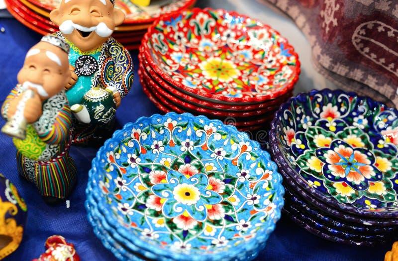 Ceramische platen en cijfers van Oezbekistaanse mensen n in traditionele kleding - robe en een skullcap, geschilderde platen stock foto