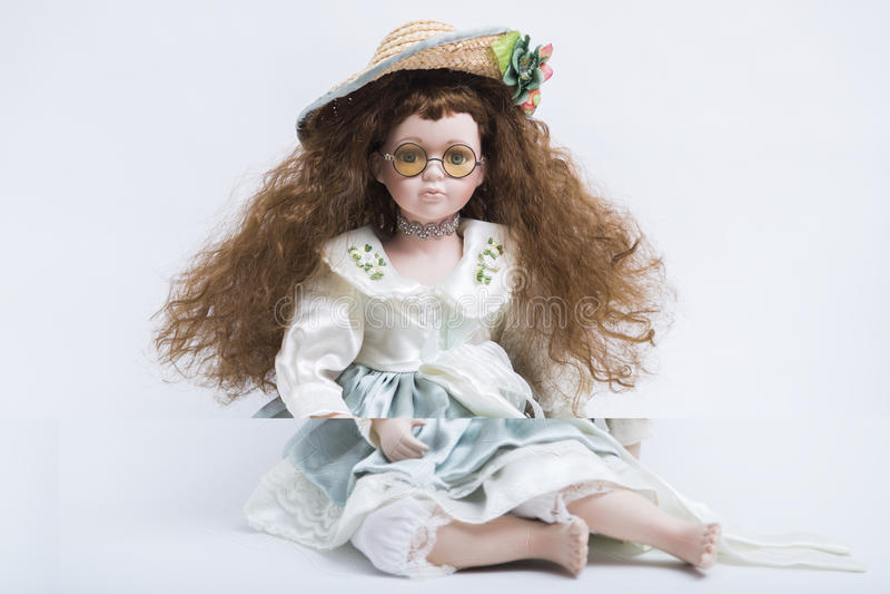 Ceramische porselein met de hand gemaakte blonde pop met rieten hoed en gele glazen stock fotografie