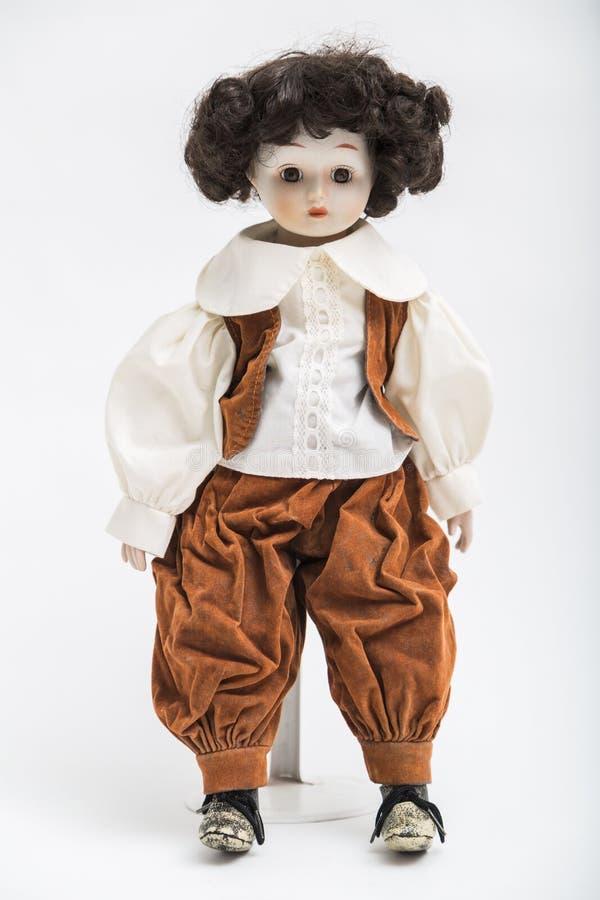Ceramische porselein met de hand gemaakte pop van een donkerbruine jongen in bruin kostuum royalty-vrije stock afbeelding