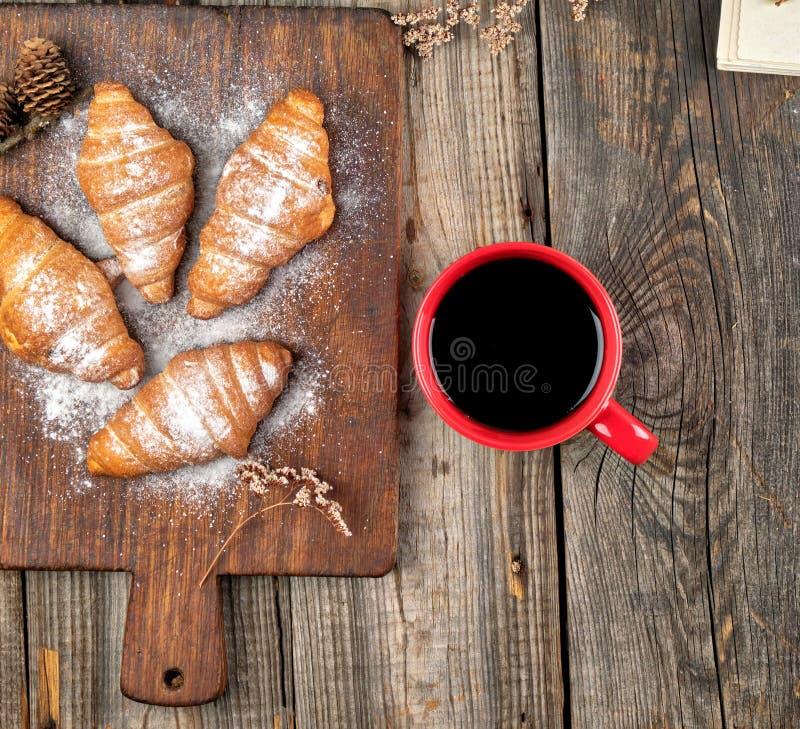 ceramische rode kop met zwarte koffie en houten scherpe raad met gebakken croissants royalty-vrije stock afbeelding