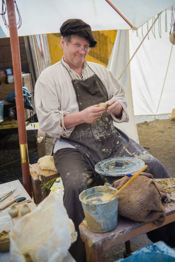 Ceramist (keramiker) på den medeltida marknaden arkivbild