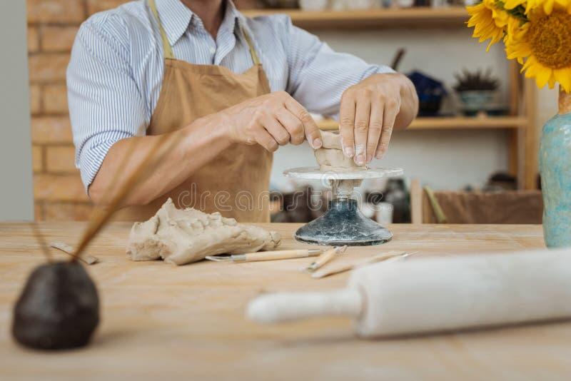 Ceramist som använder keramikgrejen som står den near vasen med solrosor royaltyfria bilder