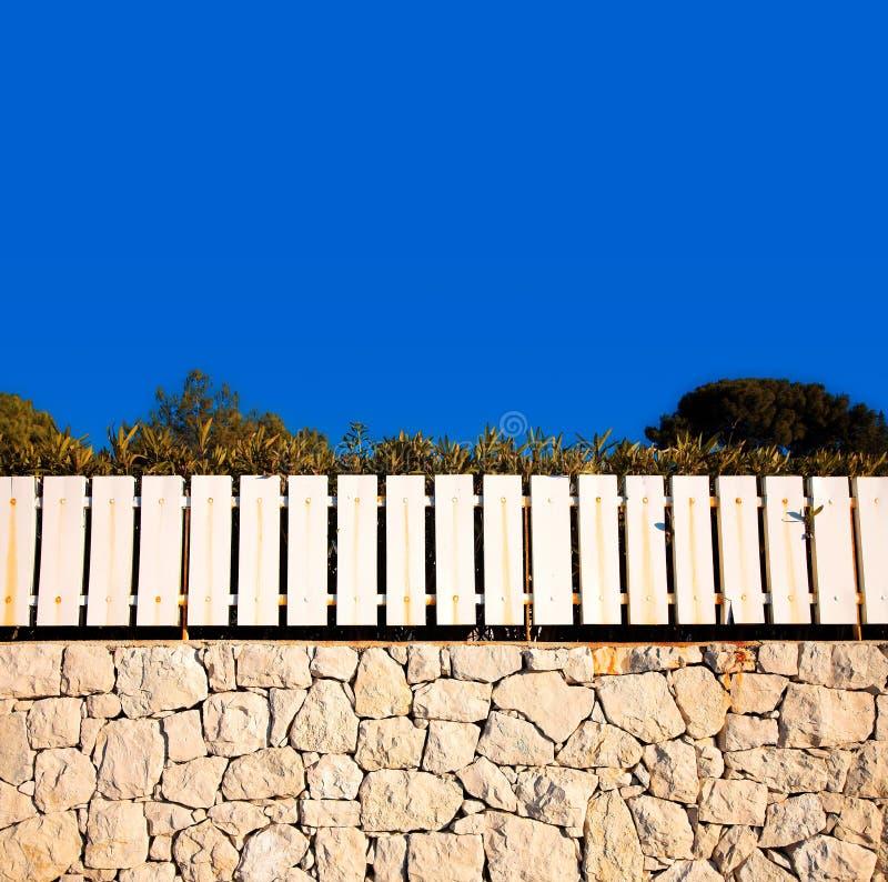 Cerca blanca en la pared de piedra fotografía de archivo libre de regalías