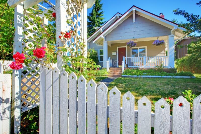 Cerca branca de trás exterior da casa cinzenta bonito velha. imagem de stock royalty free