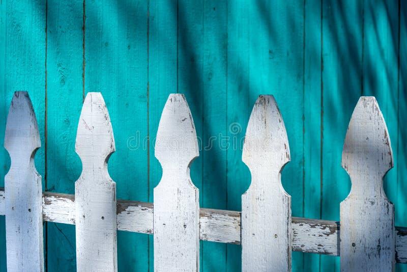 A cerca branca em pranchas de madeira azuis brilhantes pintou o fundo da parede fotografia de stock royalty free