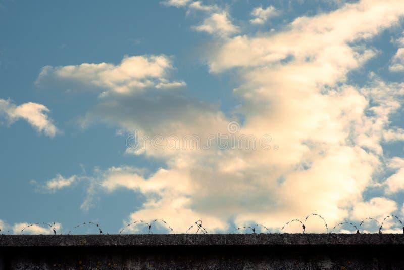 Cerca com arame farpado contra o céu imagem de stock royalty free