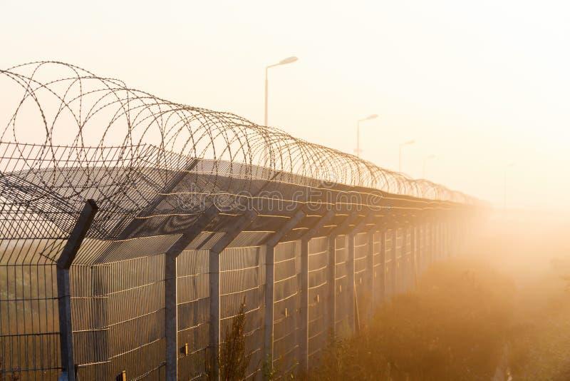Cerca con alambre de púas en la frontera foto de archivo libre de regalías