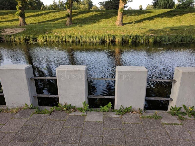 Cerca consideravelmente concreta que alinha o canal em Hoofdoprt foto de stock royalty free