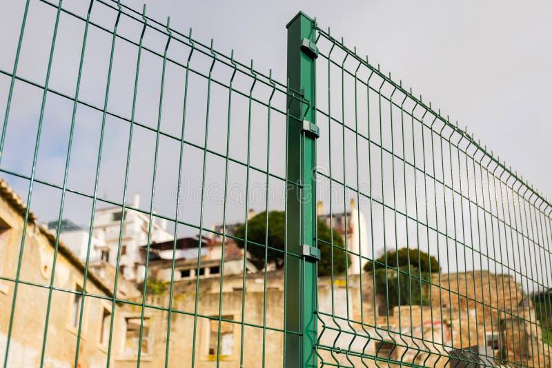 Cerca de aço da raspagem feita com fio no fundo de construção velho A instalação de cerco secional imagens de stock royalty free