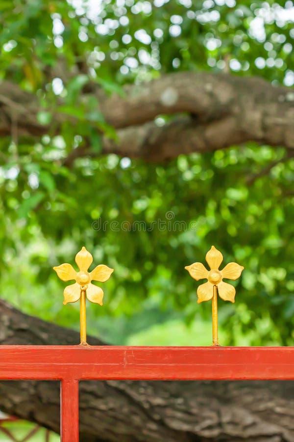 Cerca de aço decorada com as flores douradas do ferro forjado isoladas em fundos borrados da árvore fotos de stock royalty free