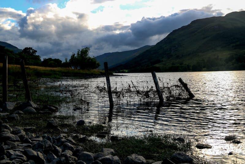 Cerca de alambre vieja en un lago escocés en la oscuridad imágenes de archivo libres de regalías