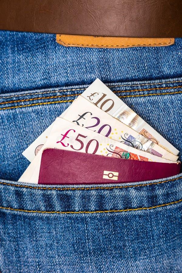 Cerca de cincuenta, veinte, diez libras esterlinas y pasaporte de la UE mirando hacia el bolsillo de los blue jeans imagen de archivo libre de regalías