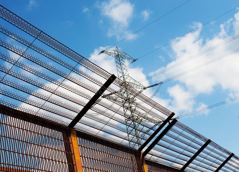 Cerca de la barrera y pilón de la electricidad contra el cielo imagen de archivo
