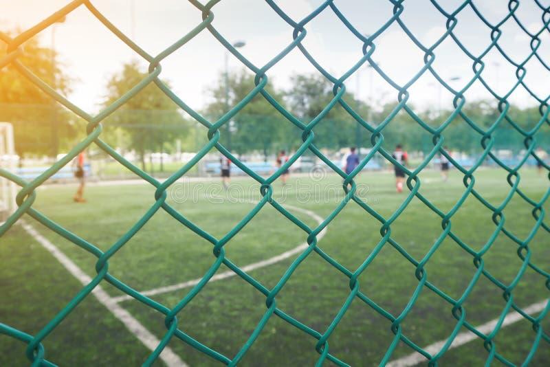 Cerca de la malla de alambre del campo de fútbol con competitivo imagen de archivo