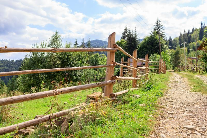 Cerca de madeira da vila nas montanhas perto da estrada de terra imagens de stock royalty free