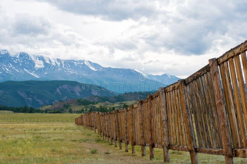 Cerca de madeira longa em um campo Na distância as montanhas imagens de stock