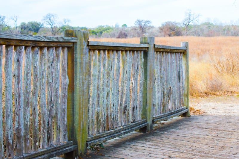 Cerca de madeira resistida em um campo da grama de pradaria dourada foto de stock