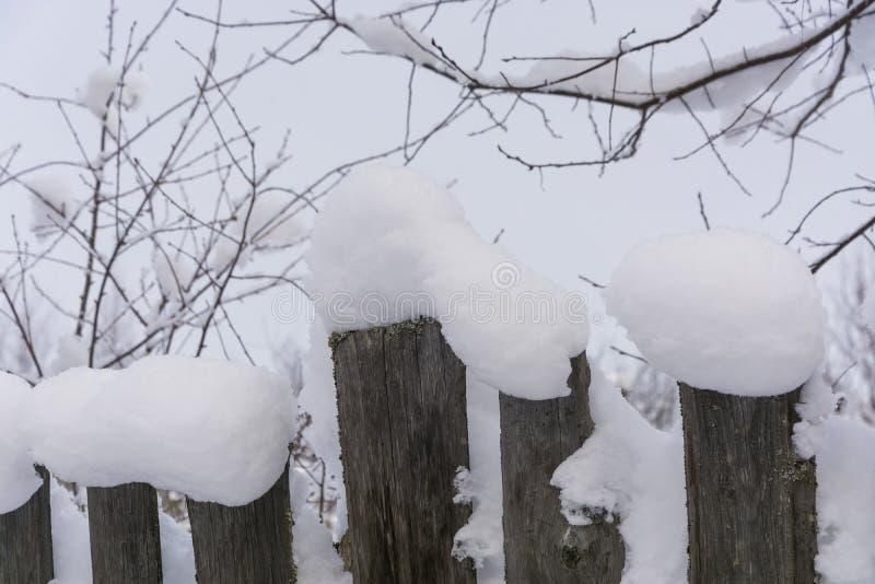 Cerca de madeira velha coberta com a neve branca em um dia de inverno imagem de stock