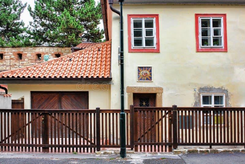 Cerca de madera de Brown en el af delantero que una casa con las tablas anaranjadas cubre imagen de archivo libre de regalías
