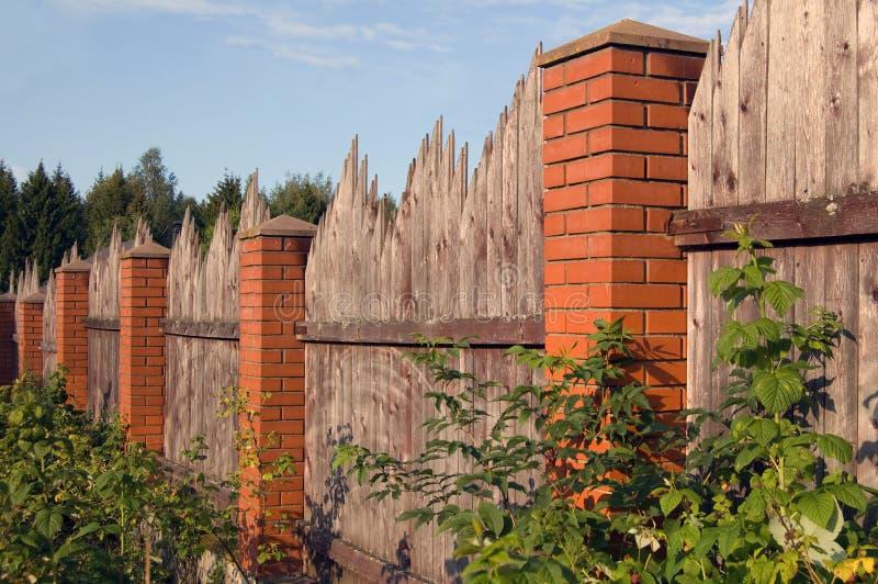 Cerca de madera con las columnas del ladrillo rojo imagenes de archivo