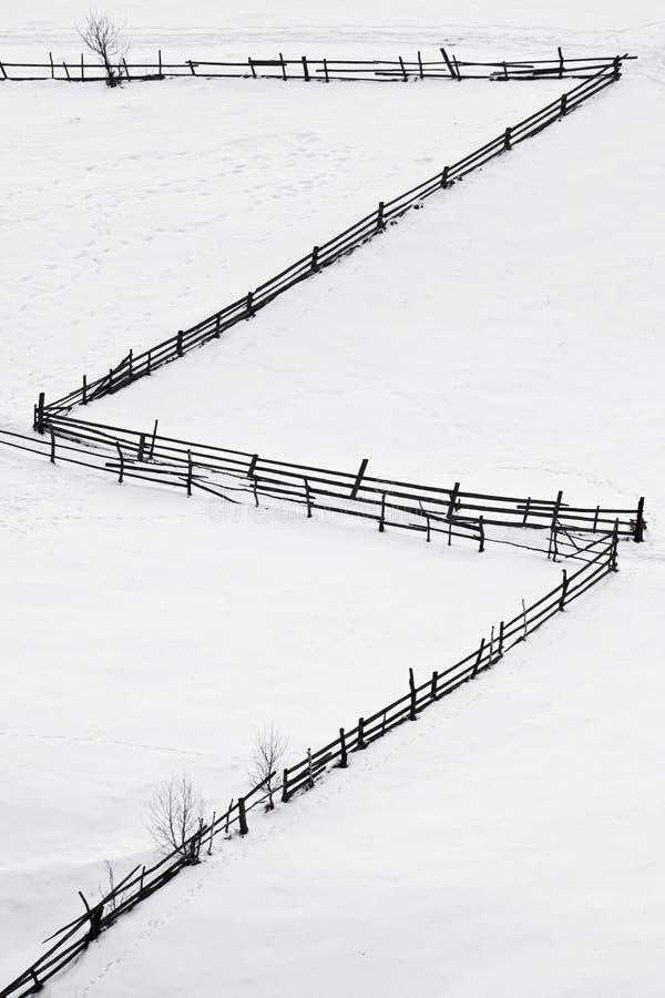Cerca de madera en la alfombra de la nieve fotografía de archivo