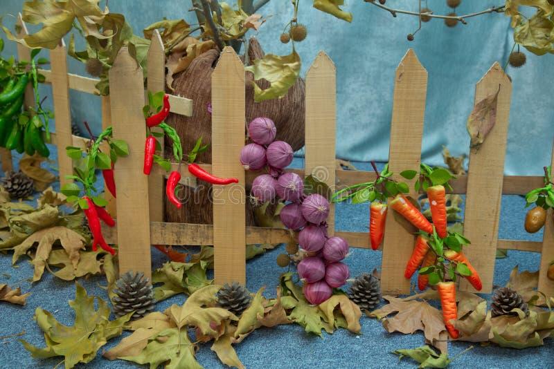 Cerca de madera Pimienta roja artificial, cebolla rosada y raíz roja Frutas y verduras artificiales en un fondo azul fotografía de archivo