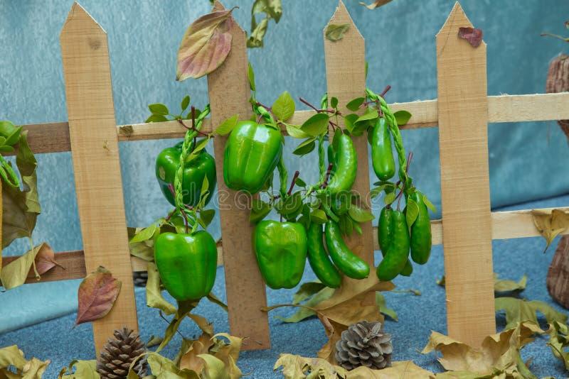 Cerca de madera Pimientas y pepinos artificiales Frutas y verduras artificiales en un fondo azul foto de archivo libre de regalías