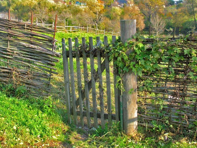 Cerca de mimbre de ramitas y de la puerta de madera fotos de archivo libres de regalías