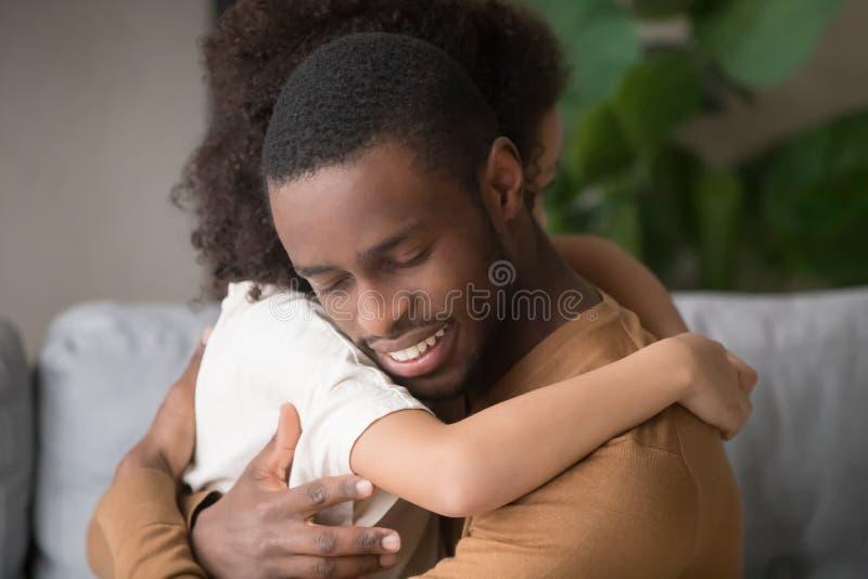 Cerca de papá negro y abrazo de hija mostrando amor fotografía de archivo
