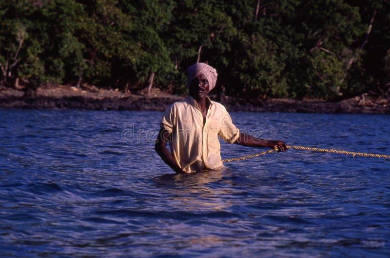 Cerca de Port Blair, islas de Andaman, la India, circa octubre de 2002: Pescador que tira de la red del océano imagenes de archivo