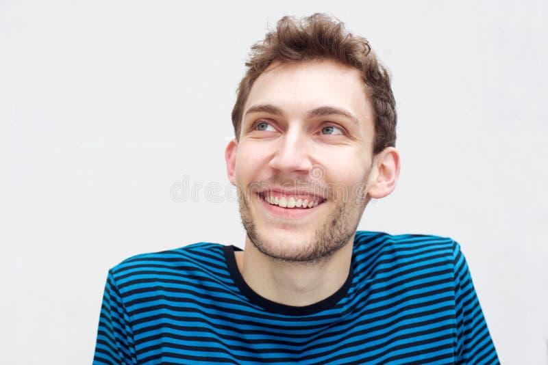 Cerca de un joven feliz sonriendo y mirando hacia arriba con un aislado fondo blanco fotografía de archivo libre de regalías