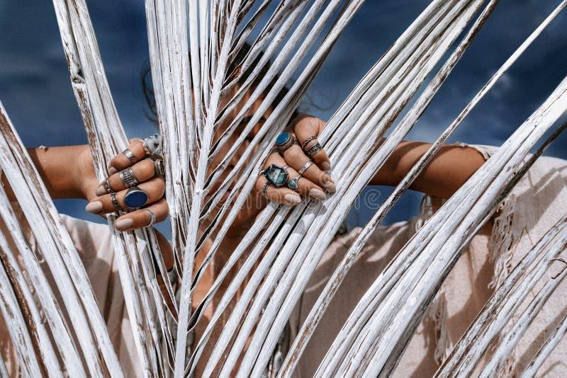 Cerca de una hermosa joven mujer de estilo tribal con muchos accesorios detrás de hojas de palma blancas pintadas fotos de archivo