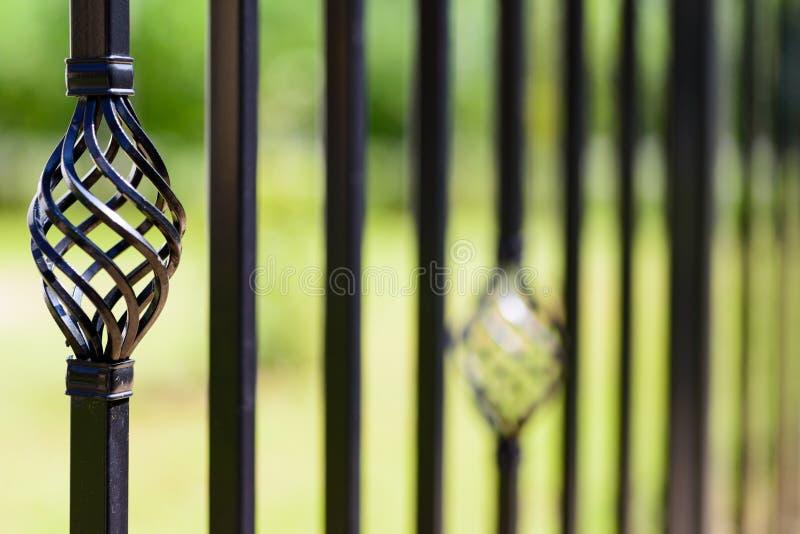 Cerca decorativa preta do metal, hastes de ferro angulares e parte superior curvada imagens de stock royalty free