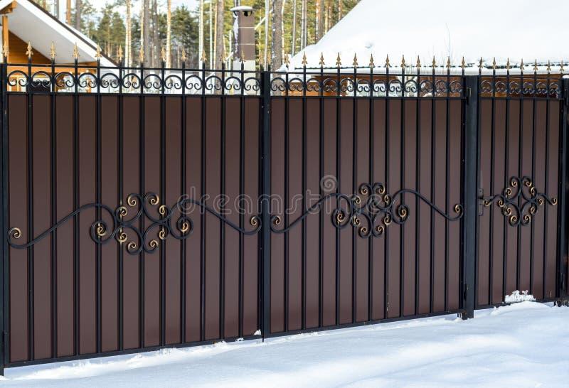 Cerca del hierro labrado con una puerta en el sector privado en una casa de campo en nieve del invierno fotografía de archivo