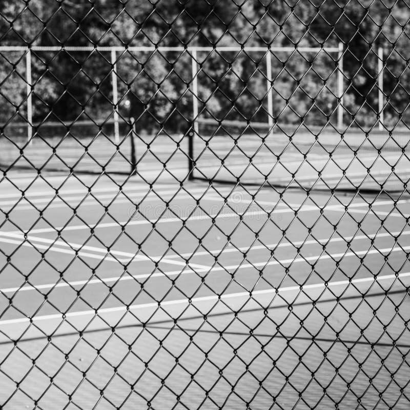 Cerca do elo de corrente com campo de tênis no fundo fotografia de stock