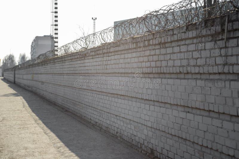 Cerca do tijolo com arame farpado acima O conceito da prisão ou da propriedade privada Arame farpado em uma parede de tijolo Cerc fotos de stock