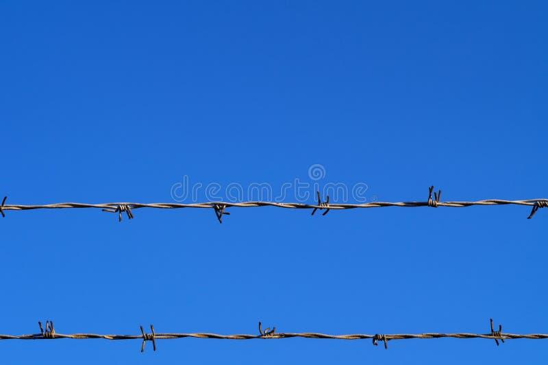 Cerca doble del alambre de púas contra el cielo azul claro con el espacio de la copia fotos de archivo libres de regalías