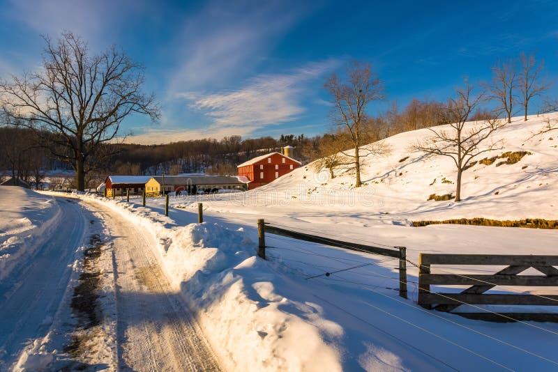 Cerca e campo de exploração agrícola ao longo de uma estrada coberto de neve em sete vales, imagem de stock