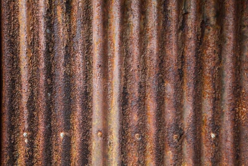 Cerca exterior textured marrom vermelha ondulada oxidada envelhecida detalhada velha da folha de metal do zinco do vintage usada  foto de stock royalty free