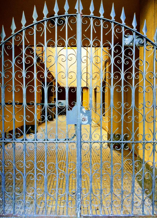 Cerca feita velha do ferro Porta esmaecida forjada do teste padrão bonito ornamentado na construção amarela imagens de stock