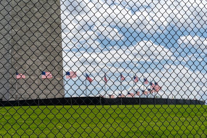 Cerca fora de Washington Monument, sob a constru??o Foco na cerca, nas bandeiras e no monumento borrados imagens de stock