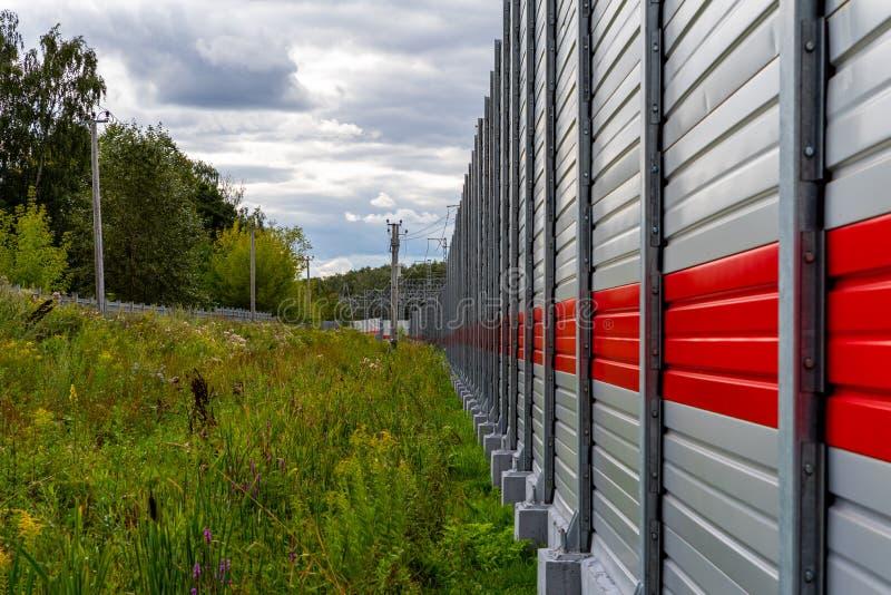 Cerca gris del metal con la raya roja, las nubes gruesas de la pre-lluvia y paisaje colorido del verano foto de archivo