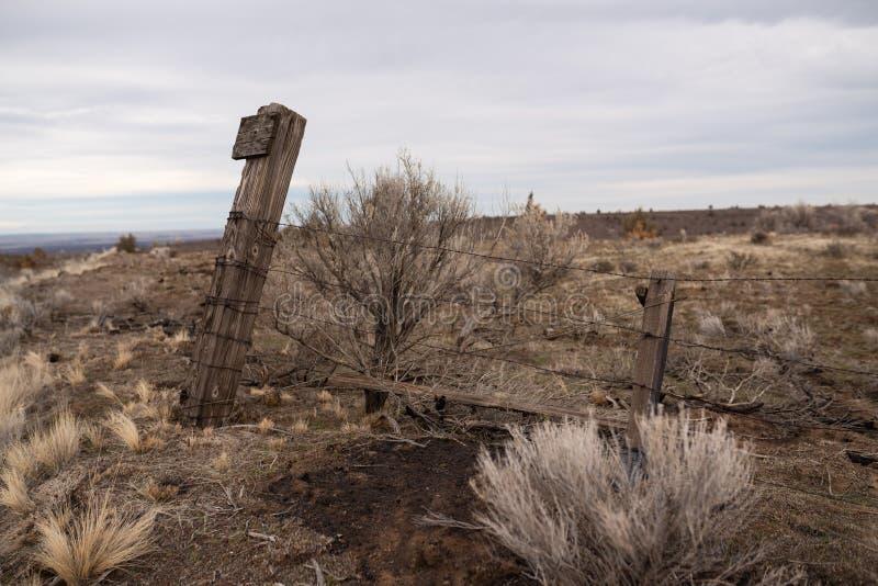 Cerca inclinada que protege tierras de cultivo estériles fotos de archivo libres de regalías