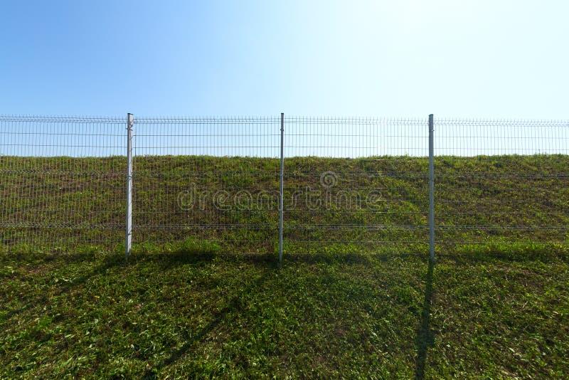 Cerca industrial de la rejilla del alambre de metal en hierba verde con el tiro granangular del fondo del cielo azul imagenes de archivo